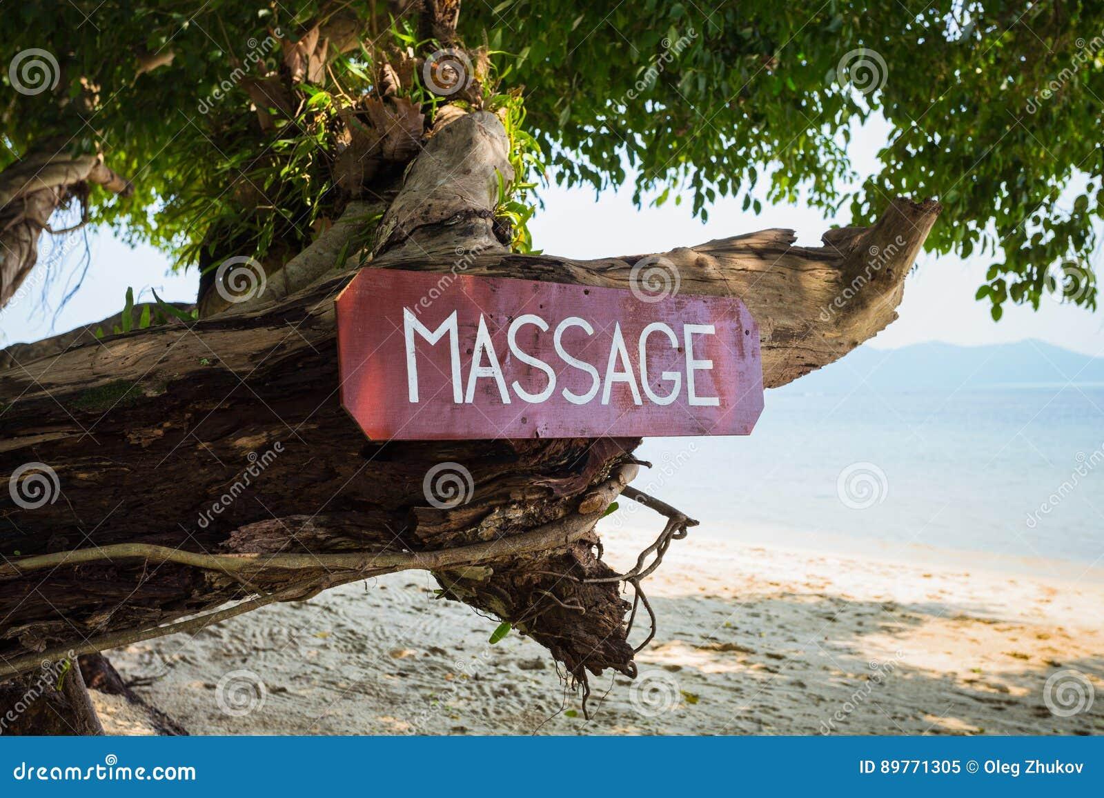 Oud uithangbord met de inschrijving, massage, op een tropisch strand
