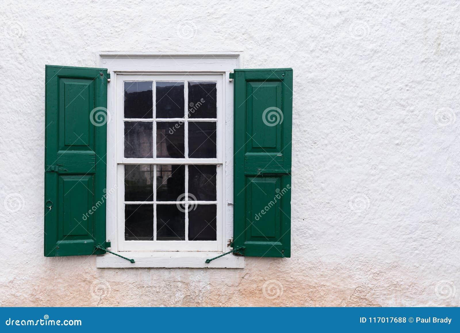 Oud venster met groene blinden