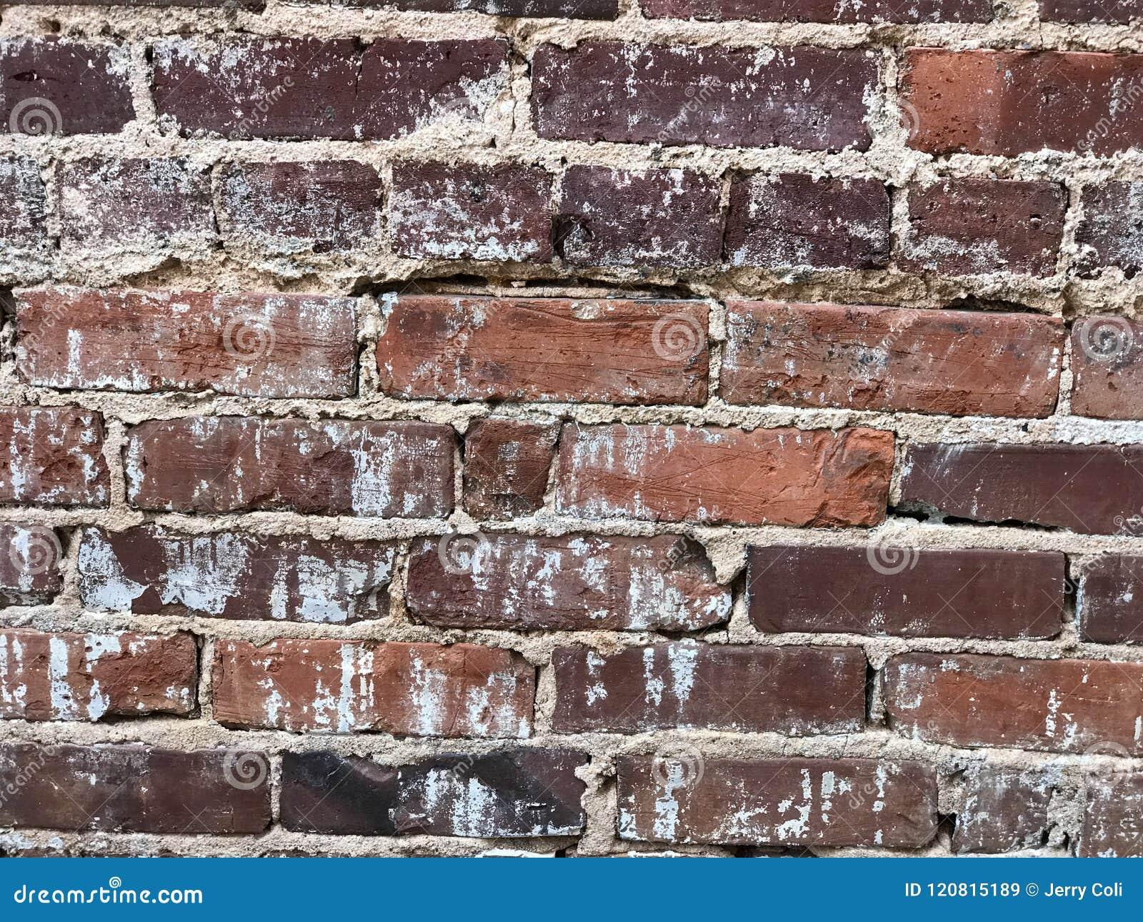 Oud waarschuw onderaan bakstenen muur met cement tekortkoming