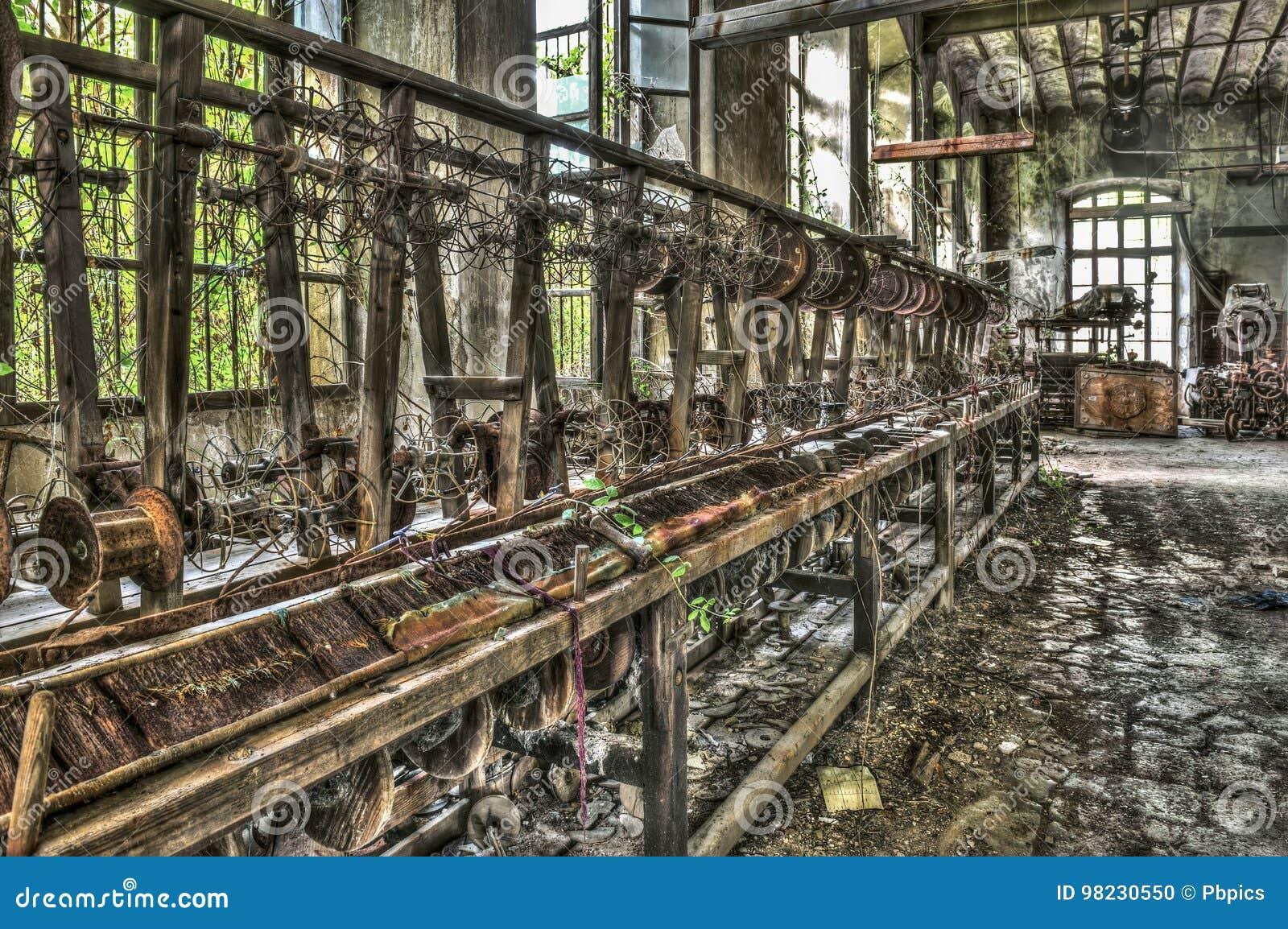 Oud wevend weefgetouw en spinnende machines bij een verlaten fabriek