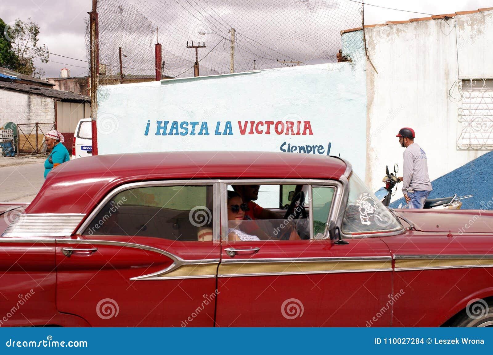 Oude auto die propagandateken in Cuba overgaan