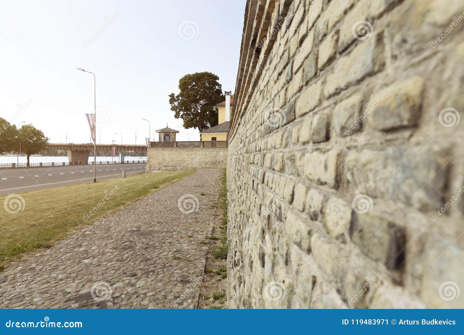 Oude bakstenen muur, omheining aan de kant van de straat in Riga, Letland