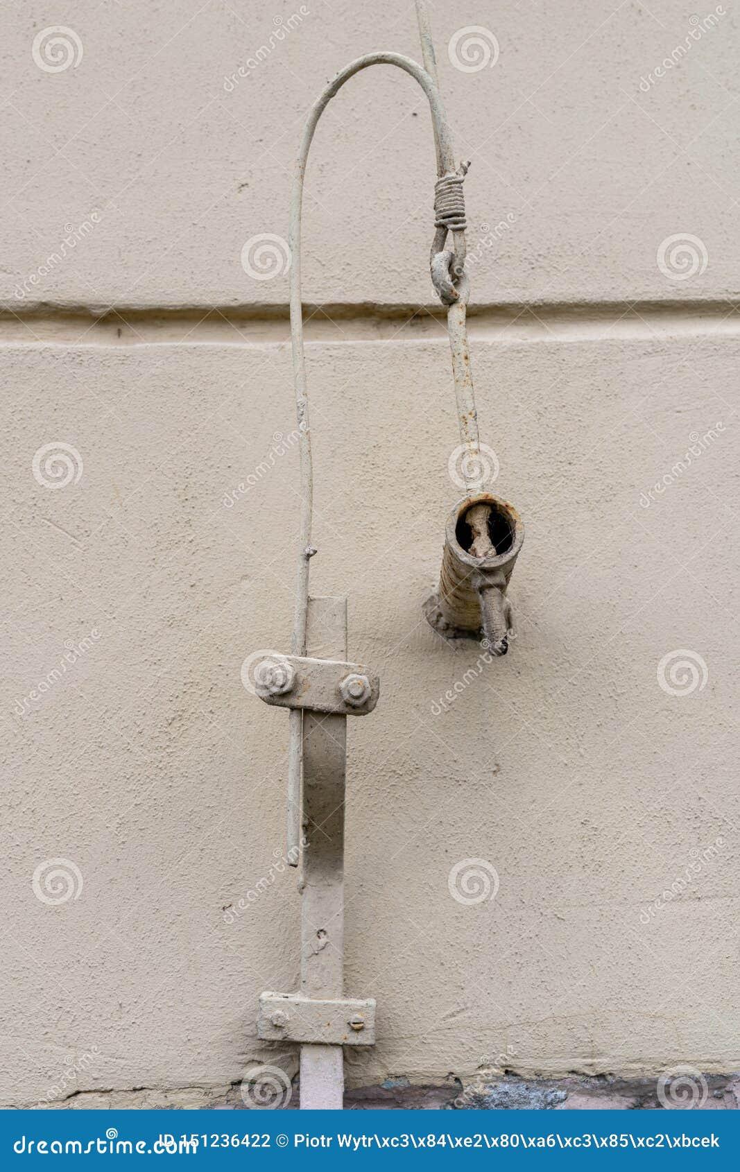 Oude bliksembescherming in een losgemaakt huis De kabels van de bliksembescherming