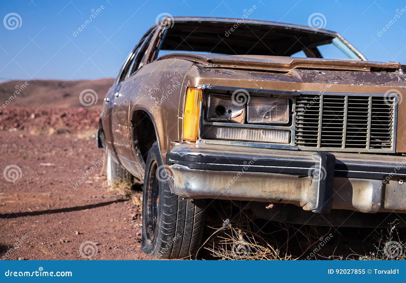 Oude bruine auto met een busted koplamp en lek band in de woestijn onder een blauwe hemel