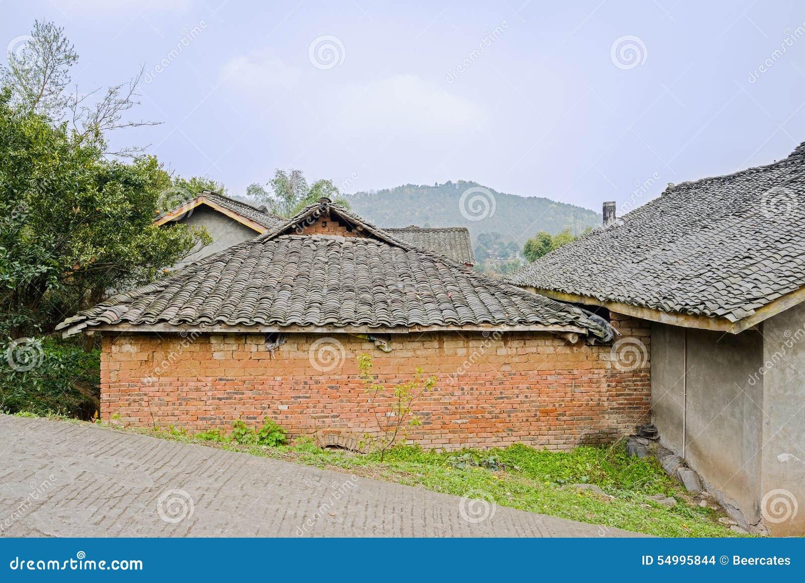 Oude Chinese boerderijen door slopy countryroad in de zonnige lente
