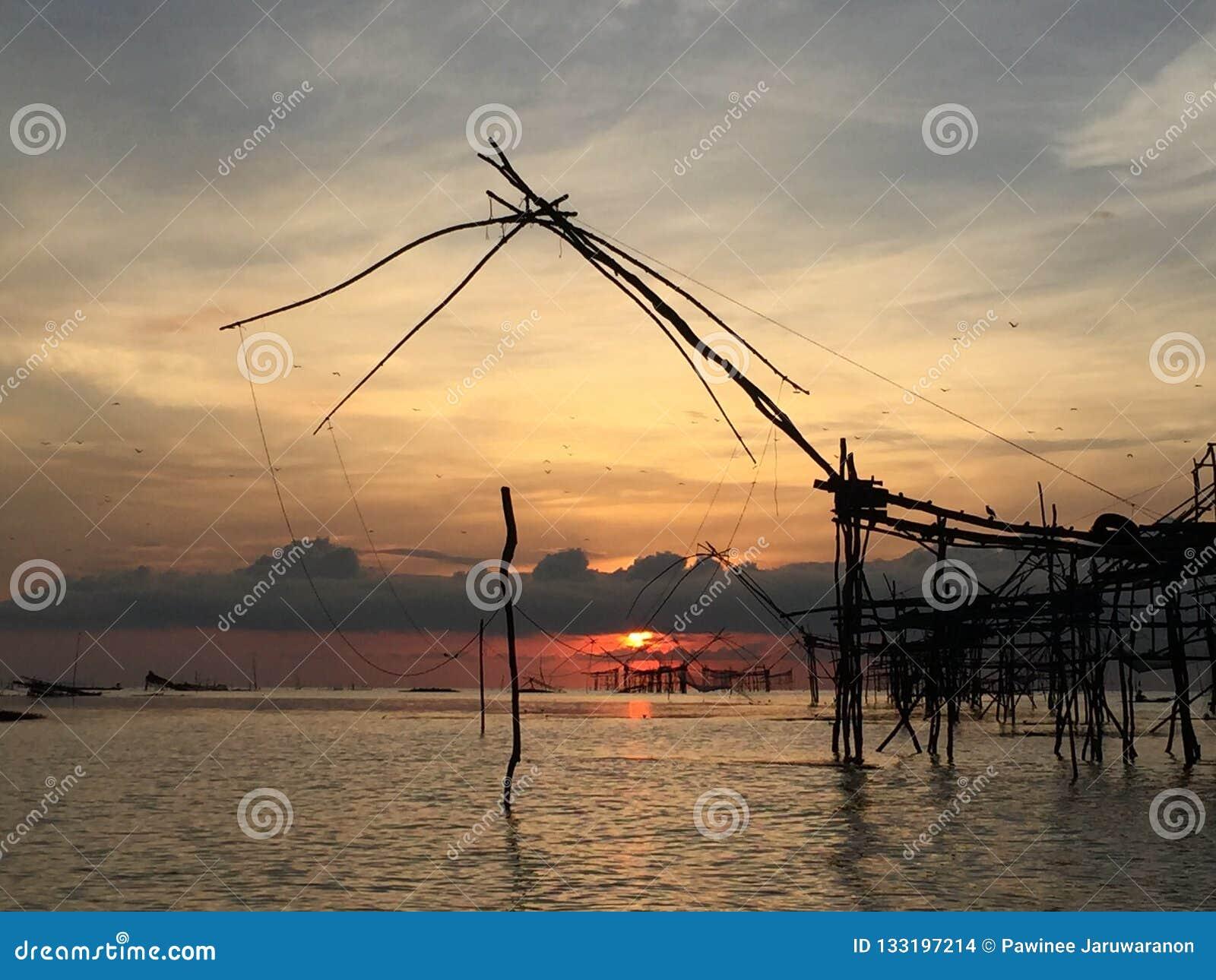 Oude cultuur traditionele visserij bij meer door houten vierkante onderdompeling netto in de zonsopgang van ochtendtijd