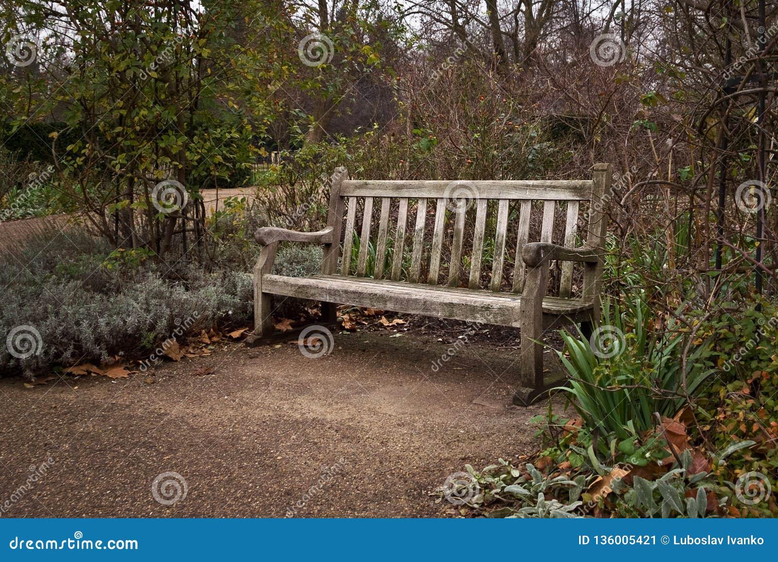 Oude eenzame houten bank bij park op koude de herfstavond