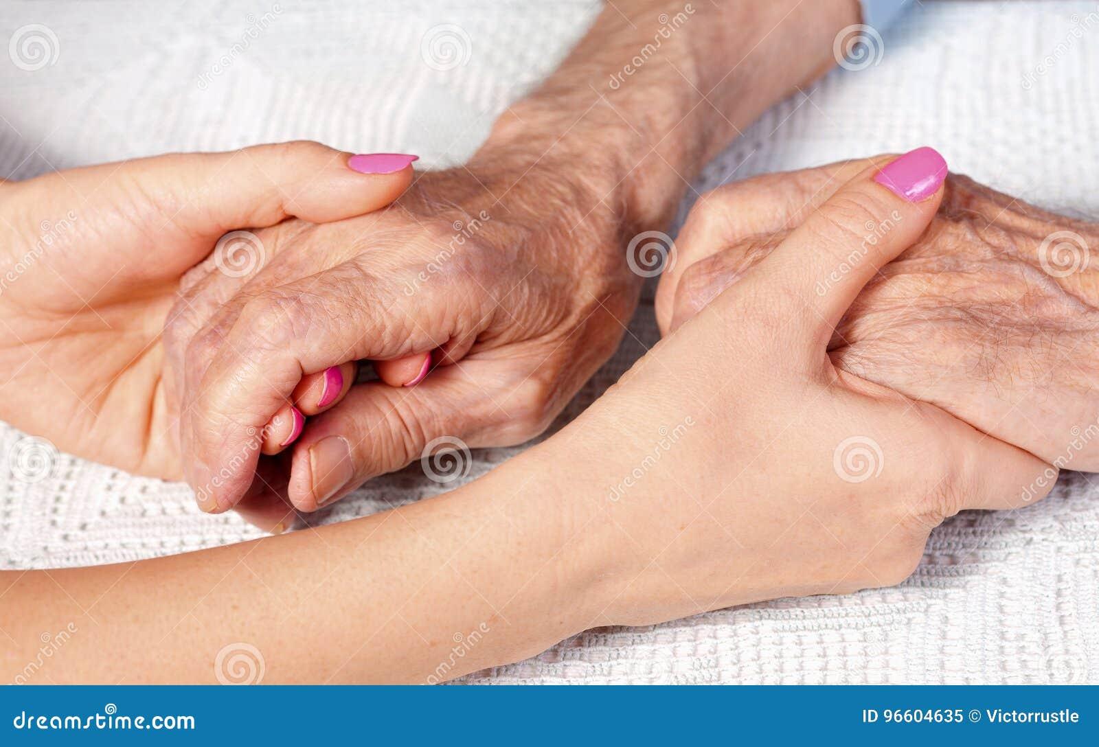 Oude en jonge holdingshanden op lichte achtergrond, close-up De zorg is thuis van bejaarden
