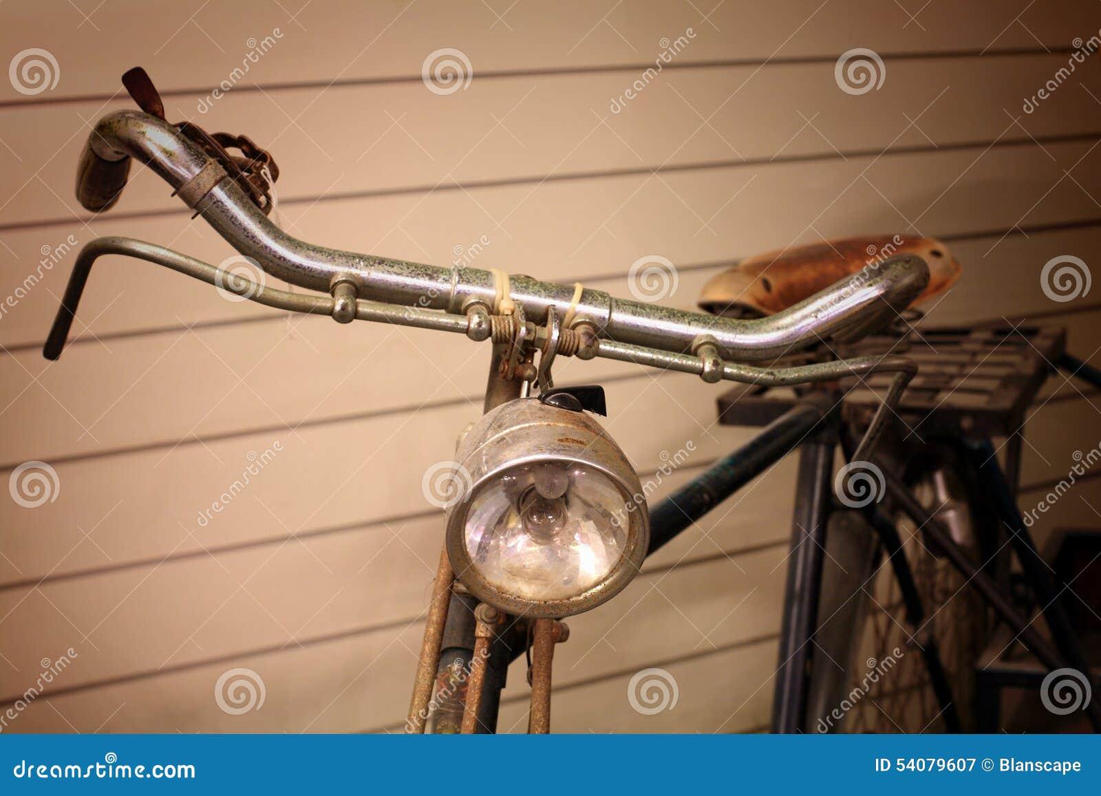Oude fiets dichtbij de houten muur