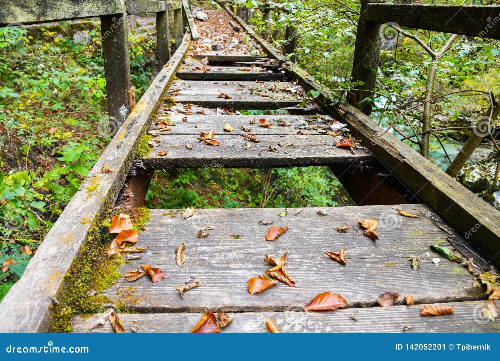 Oude gebroken houten brug met gaten gevaarlijke het lopen weg