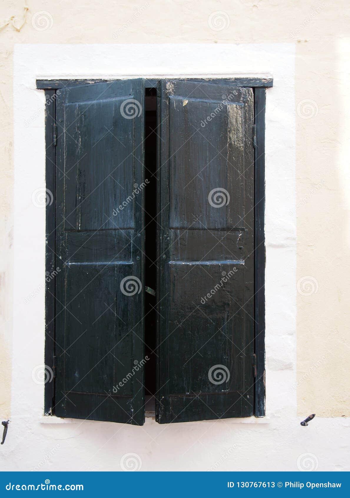 Oude gedeeltelijk open zwarte geschilderde houten vensterblinden in een wit kader op de muur van een oud Spaans huis