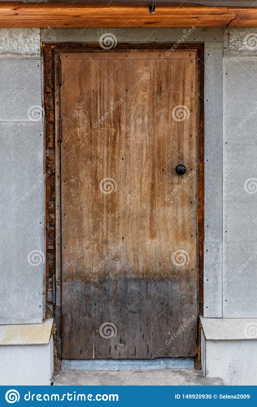 Oude gesloten houten deur Een schil, gebarsten, lichtbruine deur