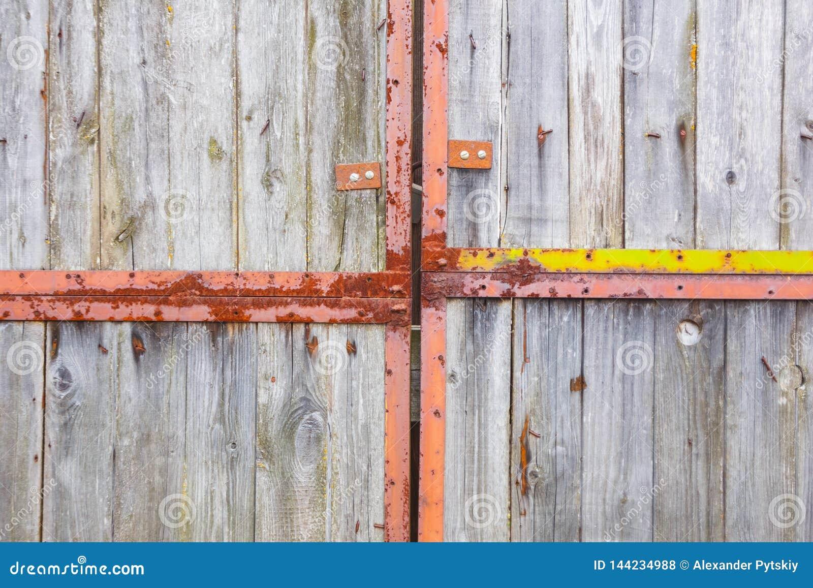 Oude grijze poort op grote roestige scharnieren