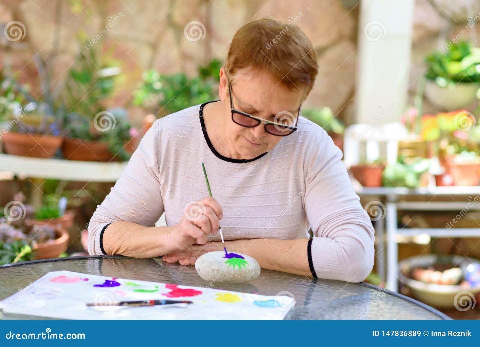 Oude hogere vrouw die pret het schilderen in kunstklasse hebben openlucht