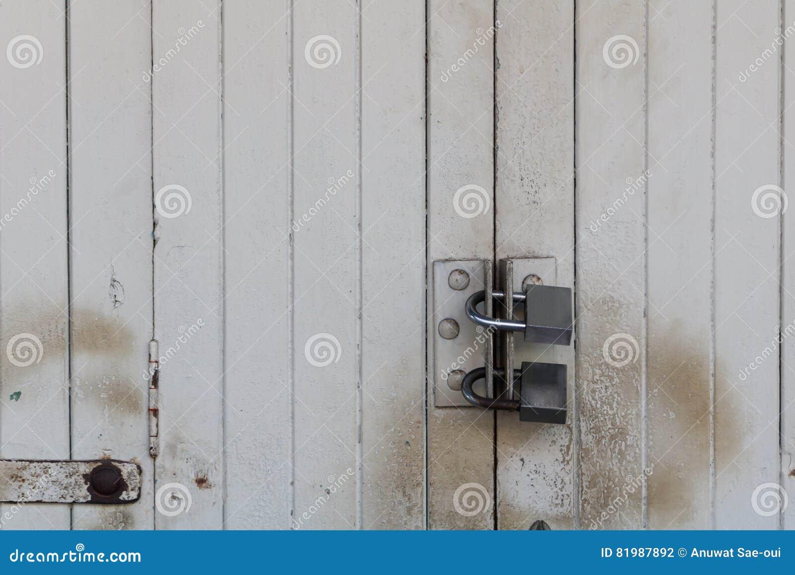 Oude houten die deur met hangslot wordt gesloten