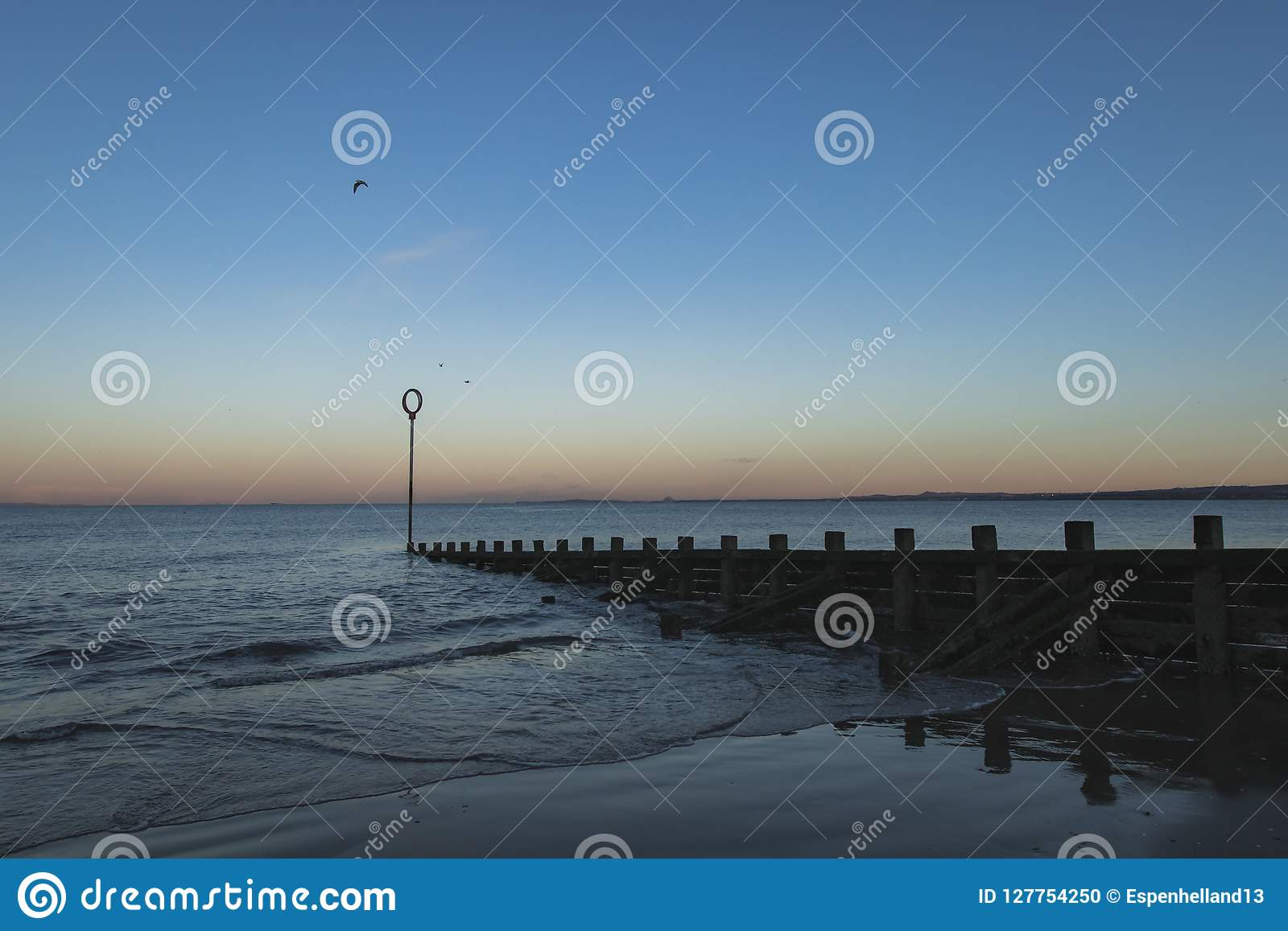 Oude houten Golfbreker op Portobello-strand bij zonsondergang