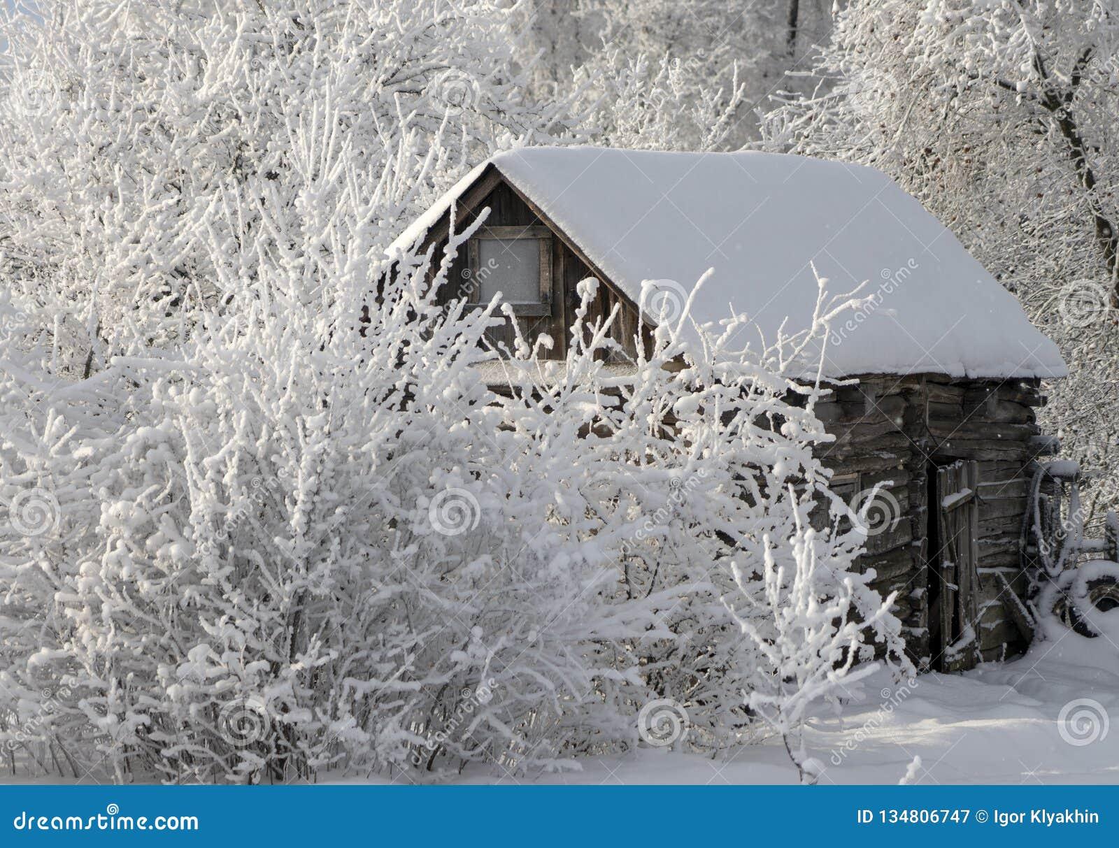 Oude houten loods tijdens een sneeuwval