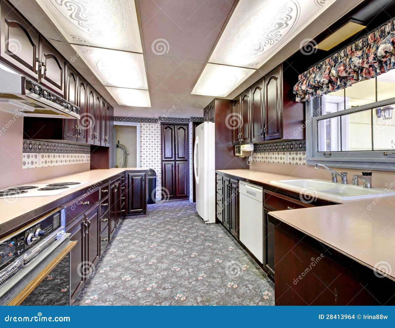 Oude houten smalle keuken met tapijt en gordijnen. stock ...