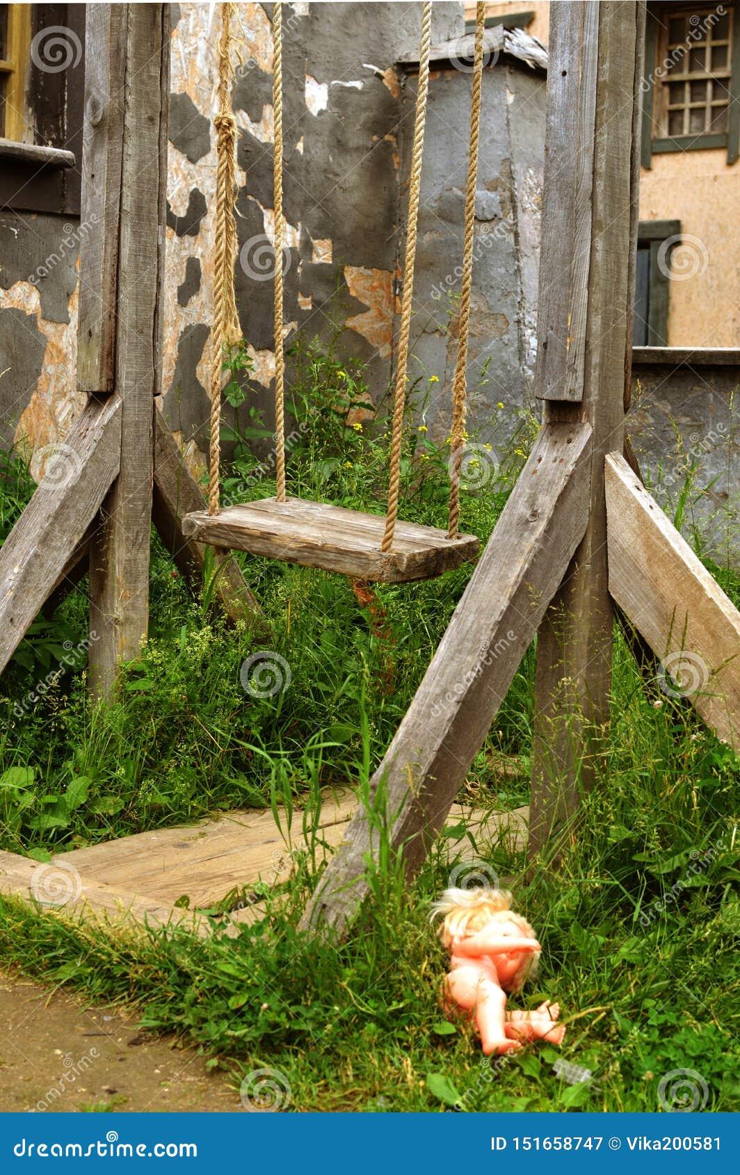 Oude houten wipplank op kabels dichtbij het gebouw zonder kinderen