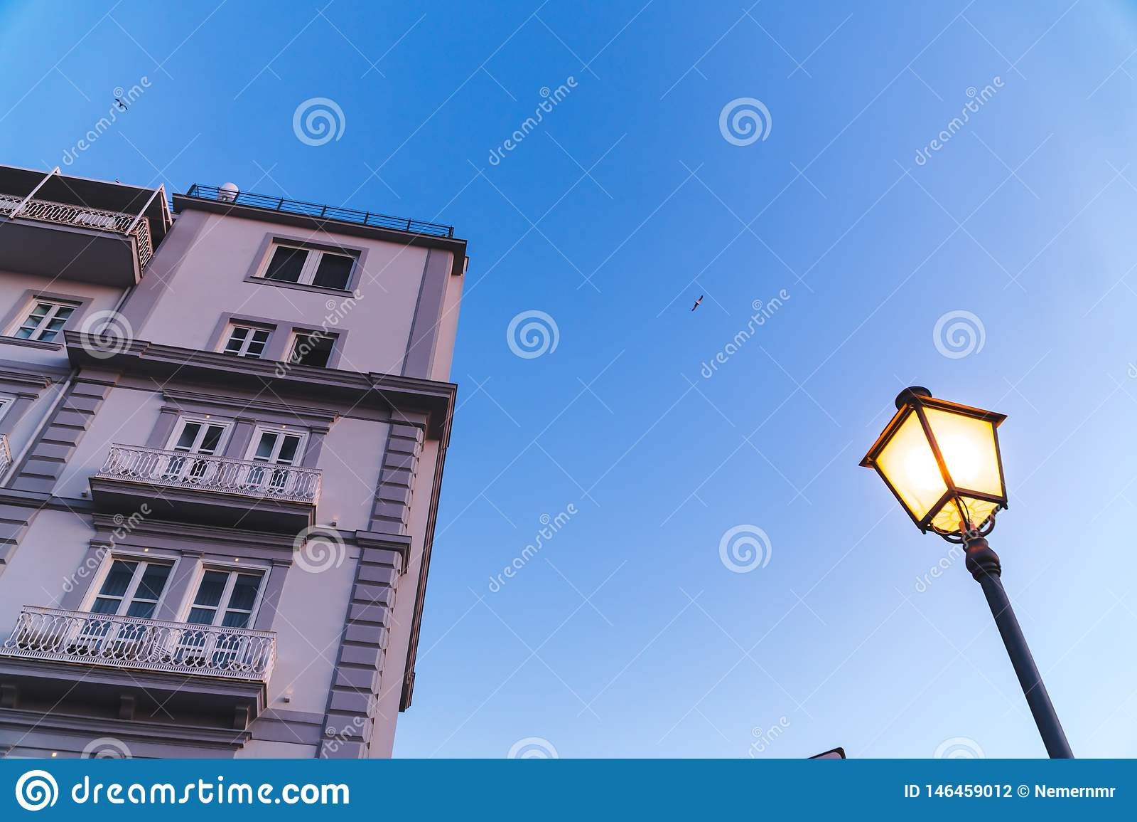 Oude Italiaanse flatgebouwen op een zonsondergang met een blauwe hemel en een straatlantaarn Voorgevel van flatgebouw, hotels, he