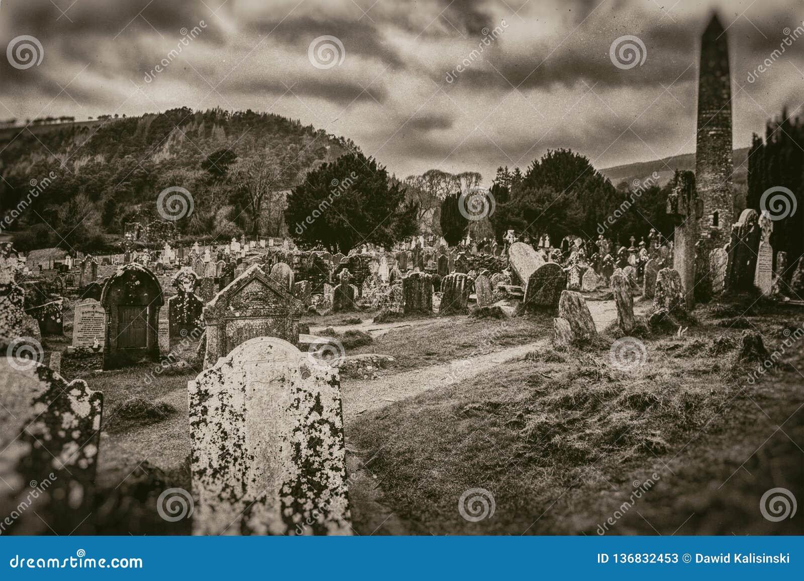 Oude oude Keltische begraafplaats en grafstenen hoge toren op berg en stormachtige hemelachtergrond in sepia stijl