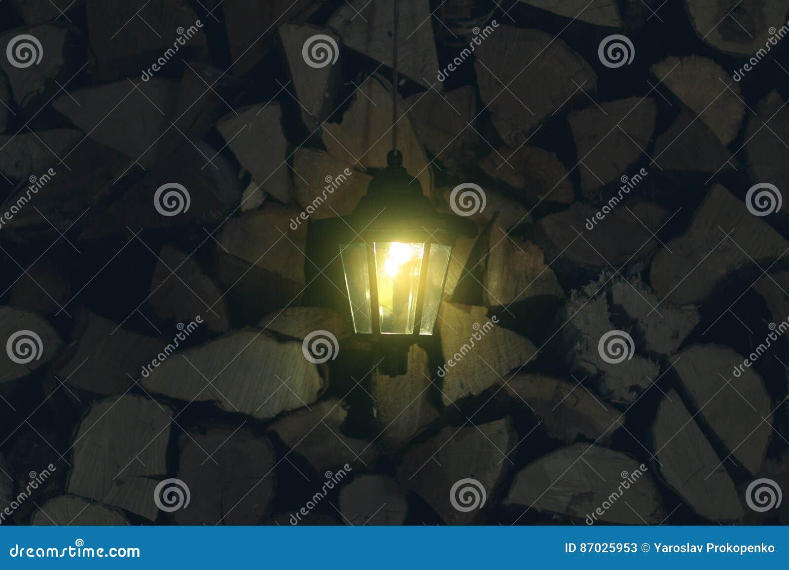 Oude lantaarn in de schuur met brandhout