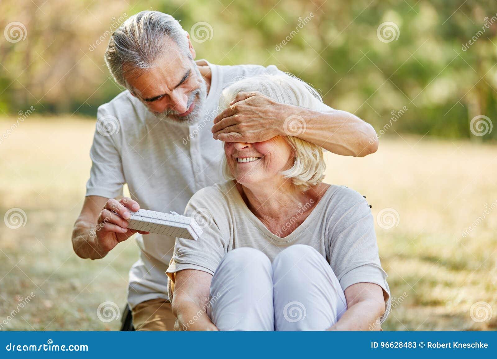 Oude Man Verrassingenvrouw Met Een Gift Stock Afbeelding
