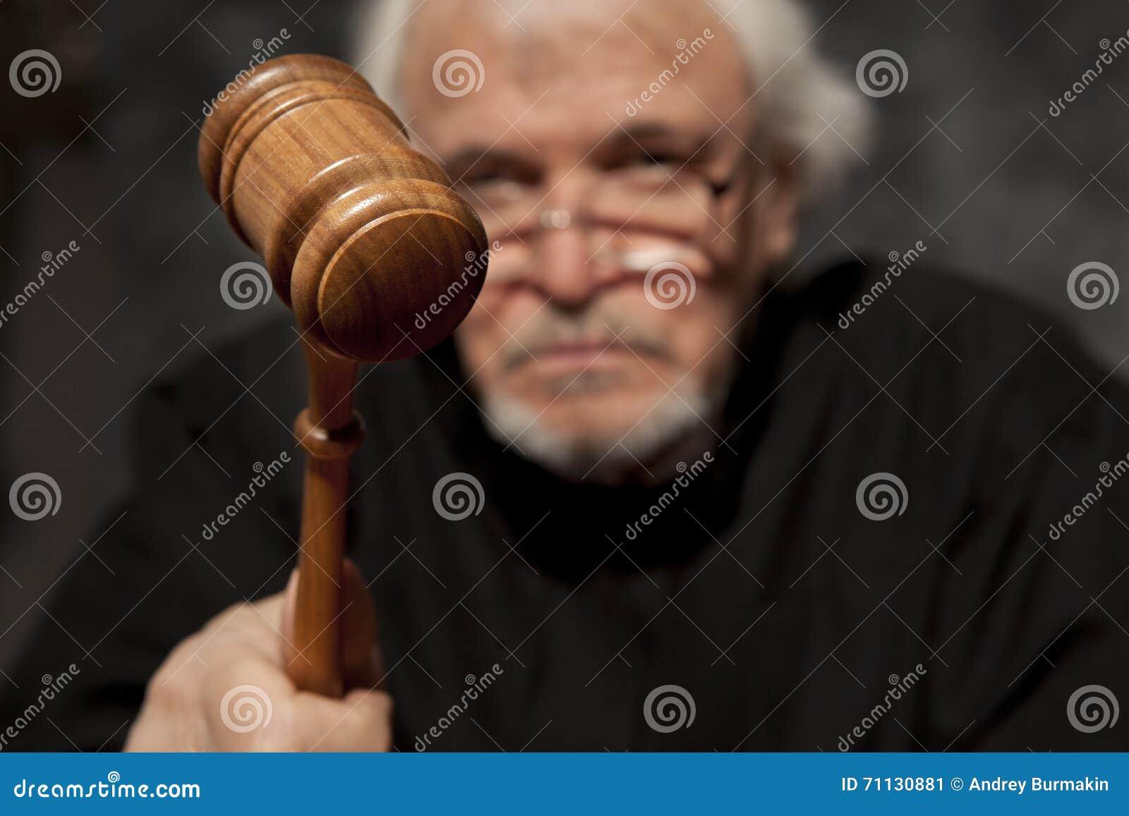 Oude mannelijke rechter in een rechtszaal die de hamer slaan