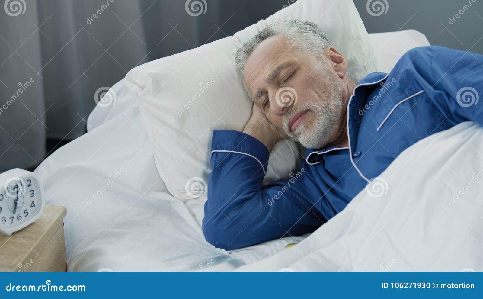 Oude mannelijke slaap in bed in de ochtend, gezonde slaap, terugwinningstijd, close-up