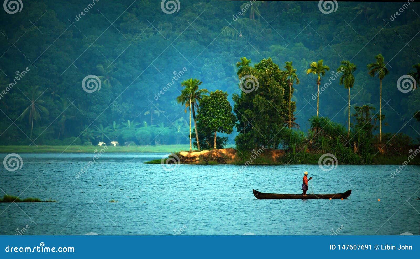 Oude mens die alleen in een boot vissen