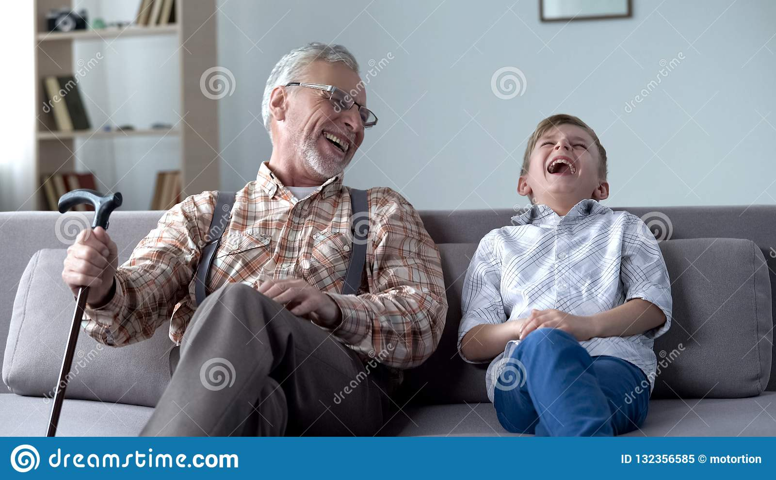 Oude mens en jongen die, samen gekscherend, waardevolle pretogenblikken echt lachen