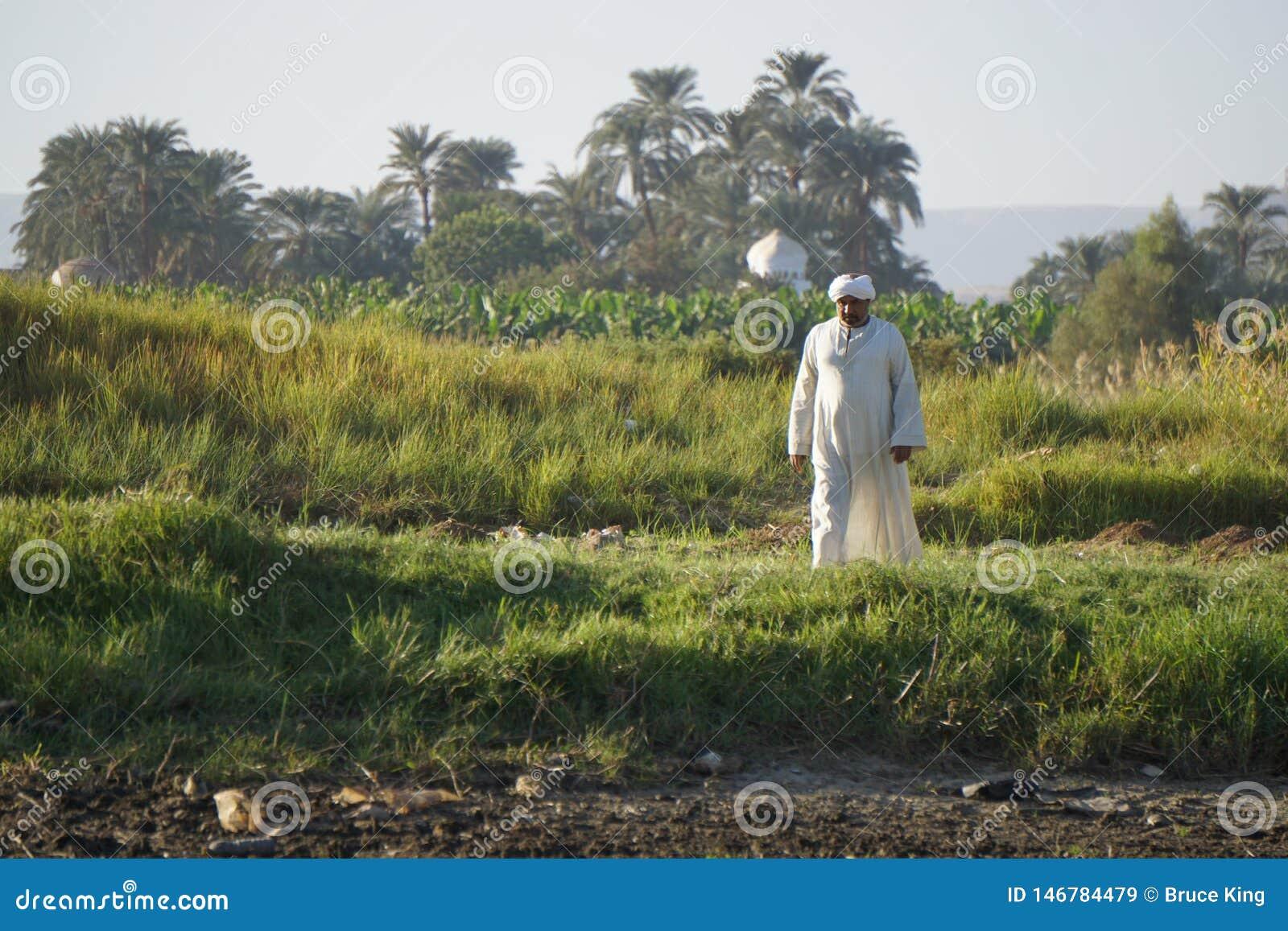 Oude mens in witte robe op de kust van de Nijl