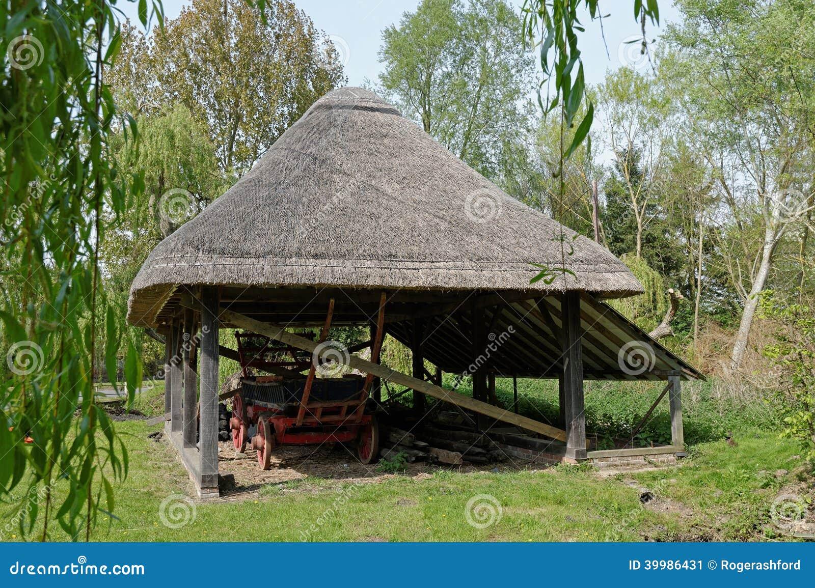 Oude met stro bedekte schuur met hay wagon stock afbeelding