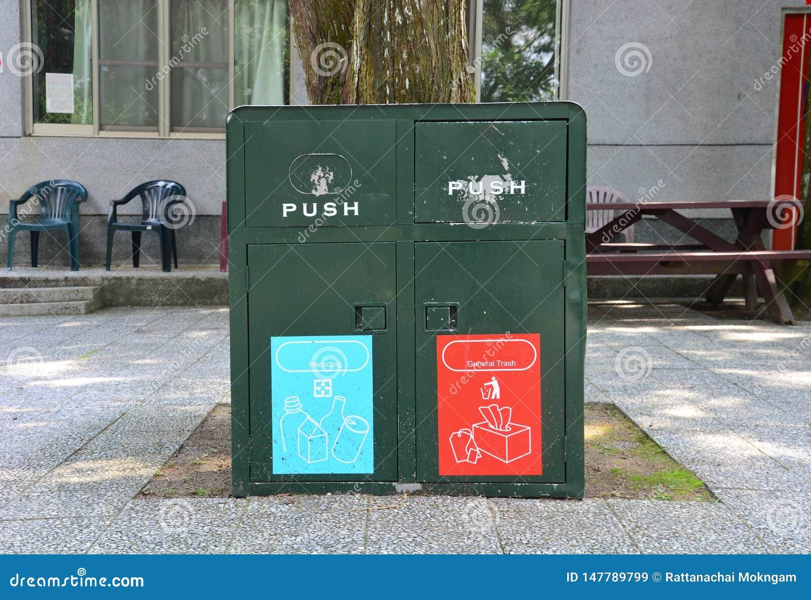 Oude metaal donkergroene bakken die in een openbare ruimte voor verschillend huisvuil recycling en algemeen afval worden gevestig