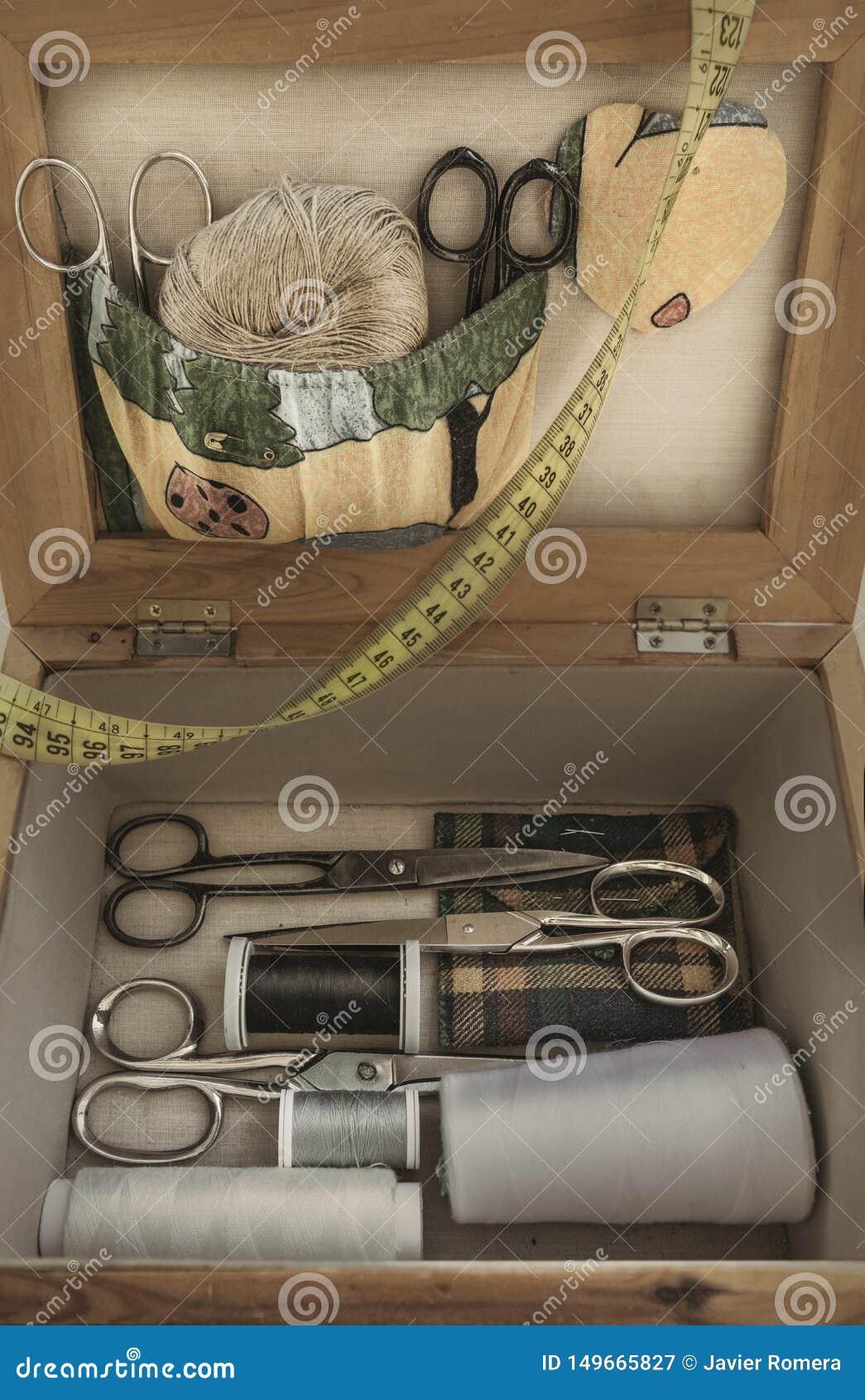 Oude naaiende uitrusting met schaar en rollen