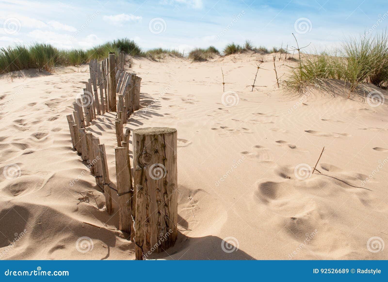 Oude omheining die een heuvel op zandig strand leiden