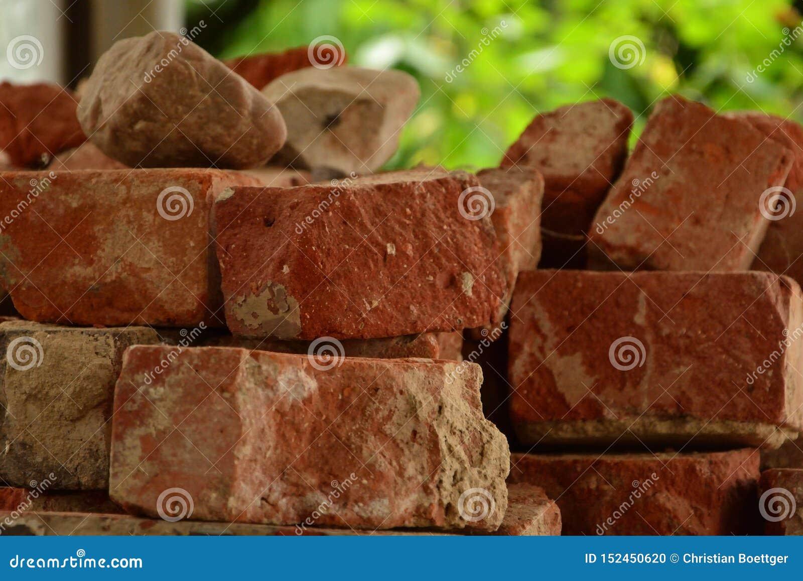 Oude rode baksteenclinker stapel in tezonlicht, gebarsten bakstenen