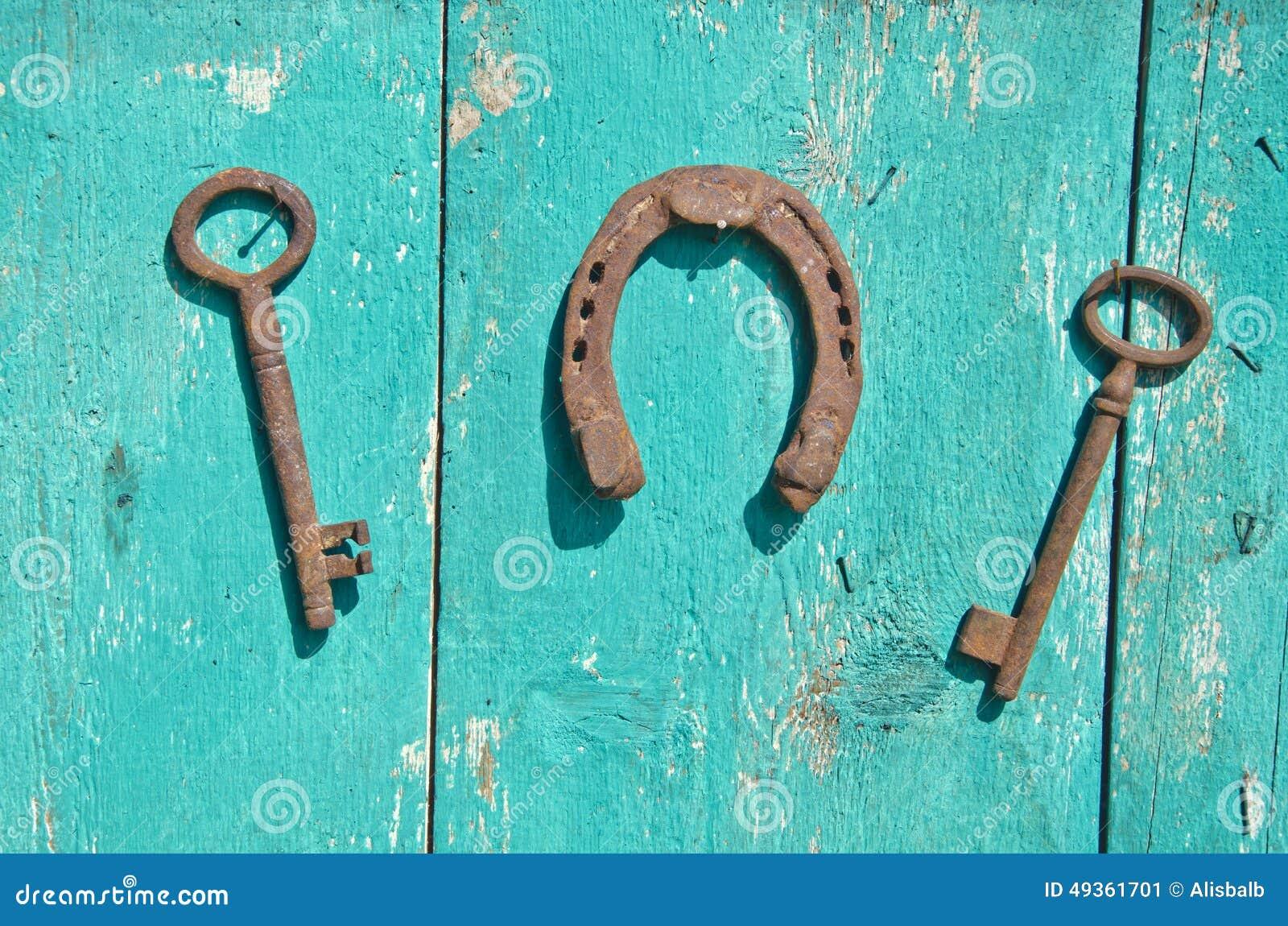 Oude roestige historische sleutel twee en geluksymboolhoef op muur