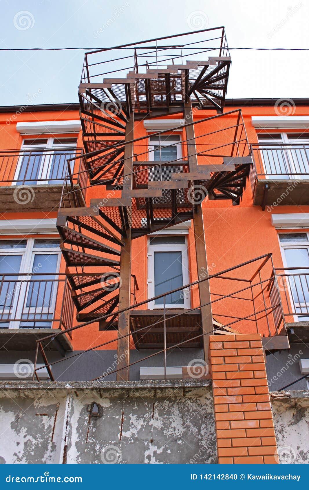 Oude roestige ijzerwenteltrap bij een helder oranje high-rise gebouw