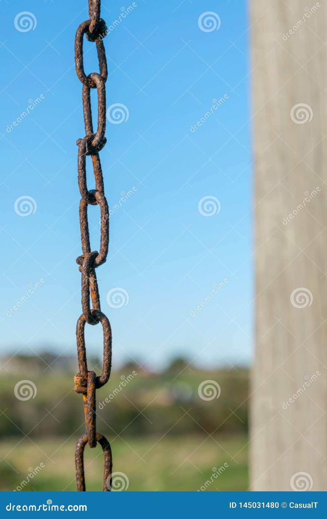 Oude roestige ketting en kettingsverbindingen, tegen een natuurlijke blauwe hemel en een groene landschaps bokeh achtergrond, Blo