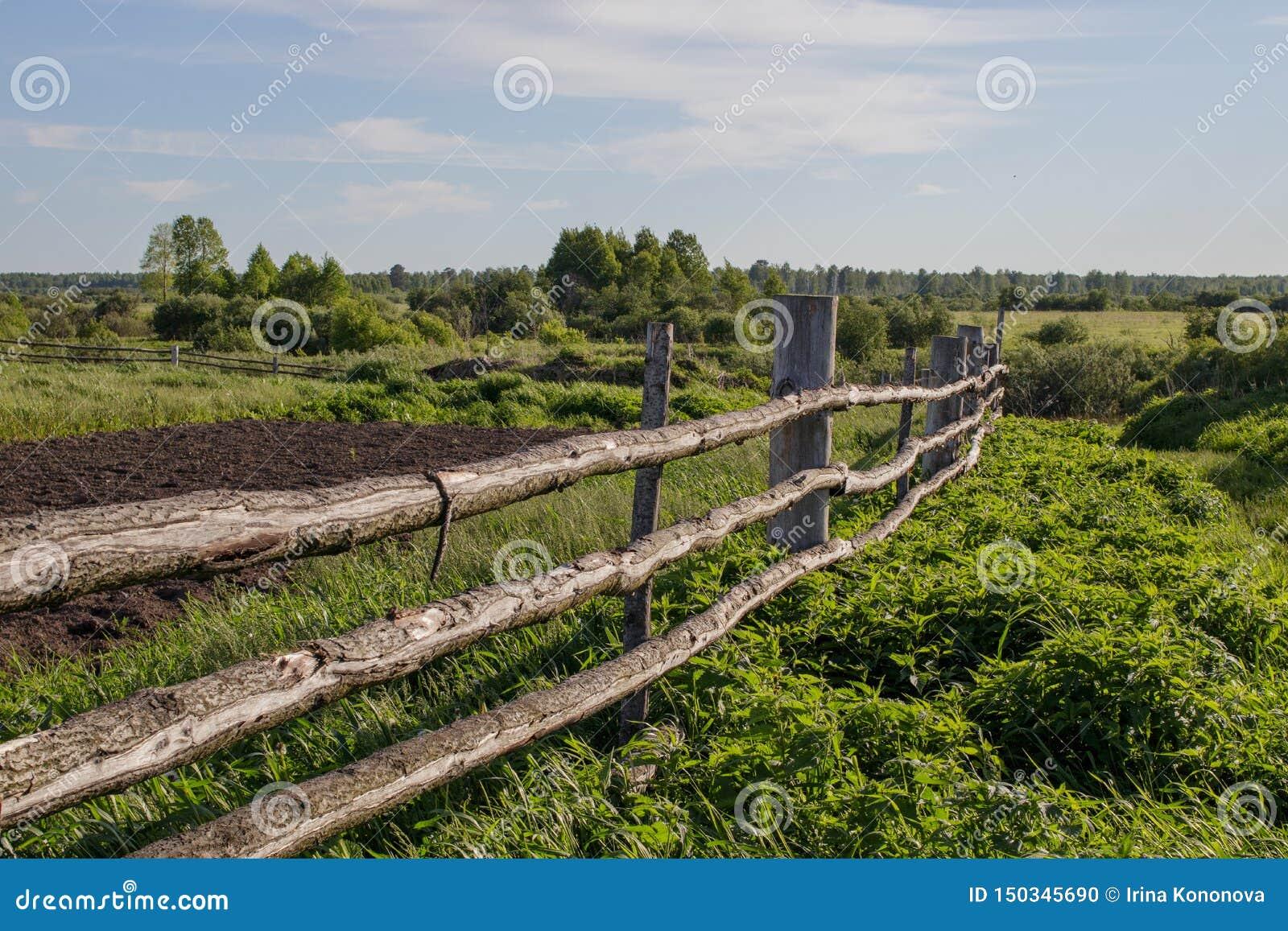 Oude rustieke houten omheining in het Siberische dorp, die zich in de afstand uitrekken
