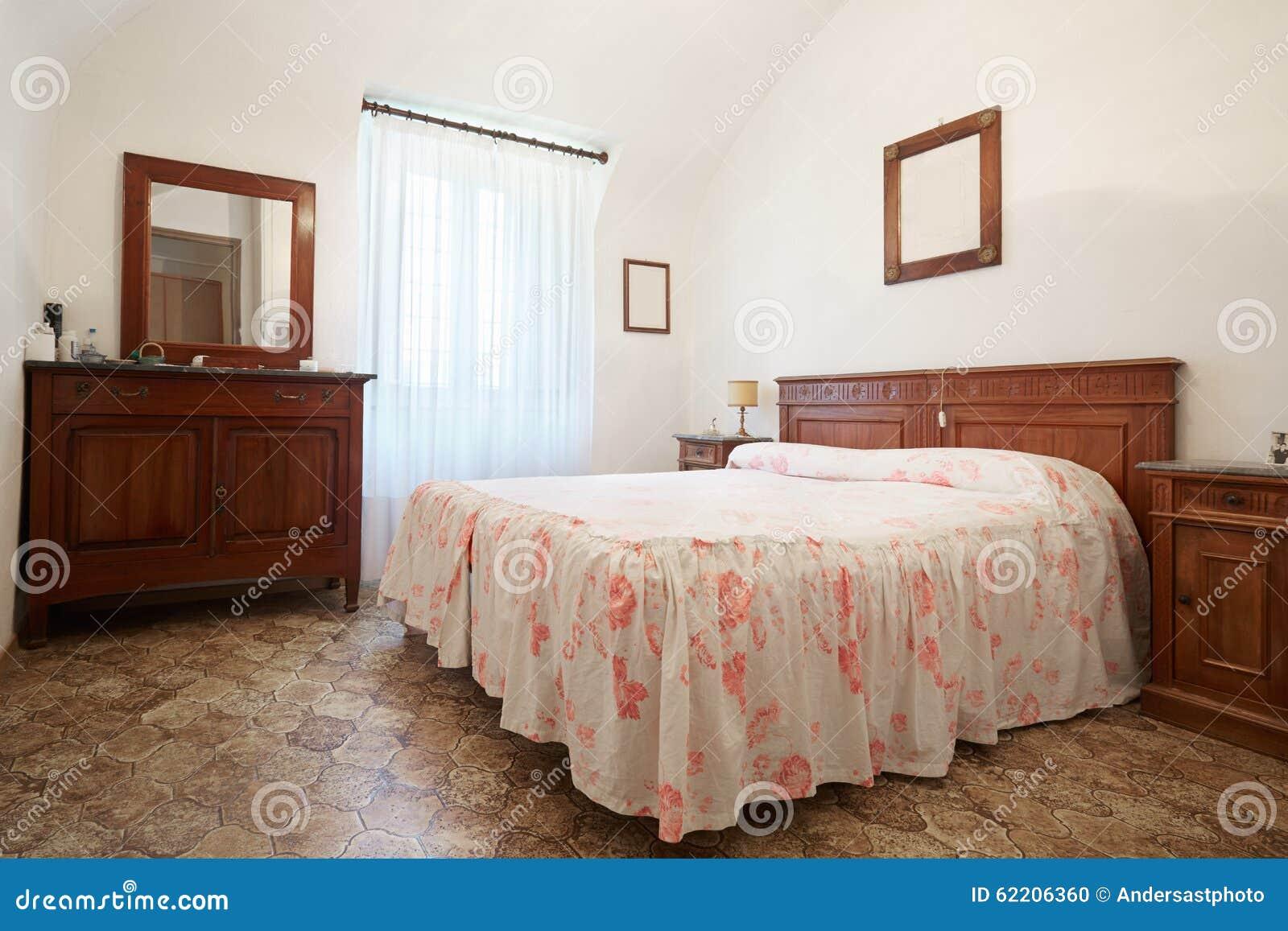 Oude slaapkamer met het bed van de koningingrootte in oud huis ...