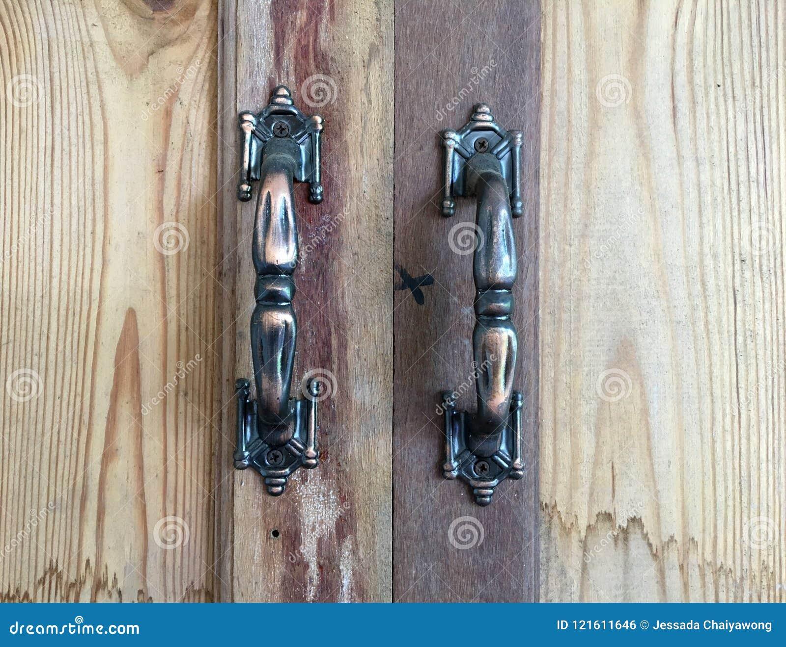 Oude staalhandvatten op houten kast