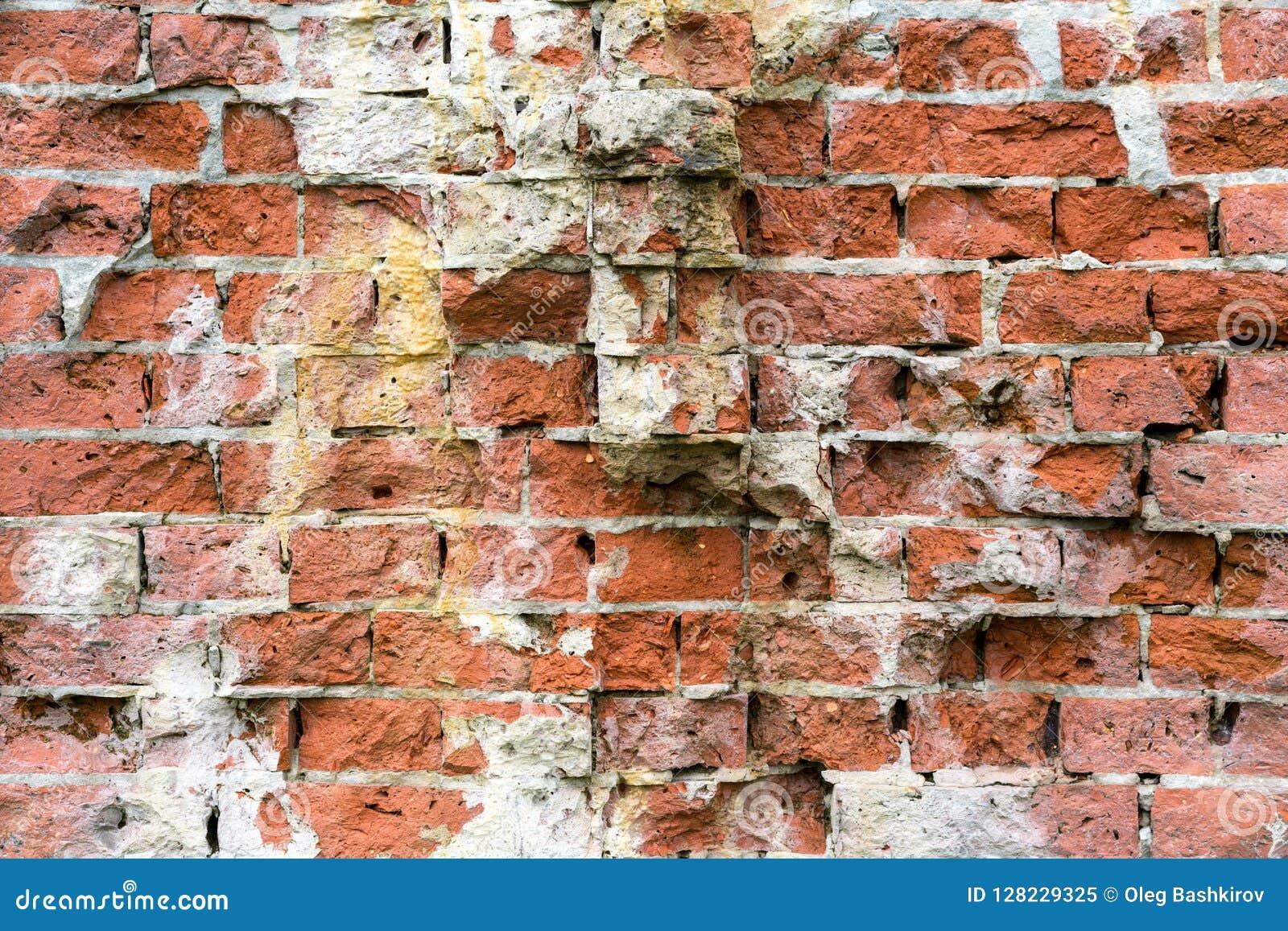 Oude streng beschadigde bakstenen muur