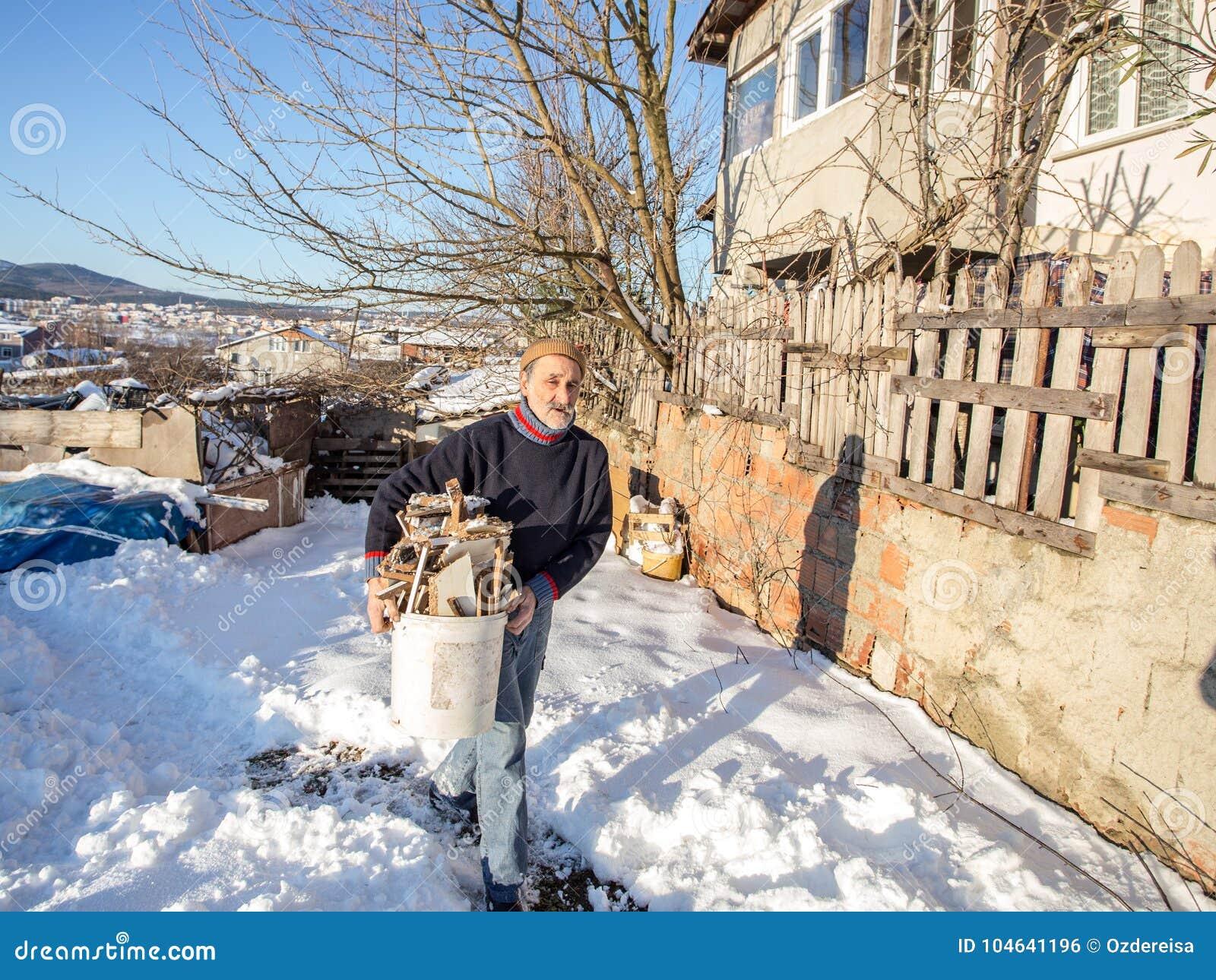 Oude Turkse mens die gehakt brandhout in een plastic emmer dragen
