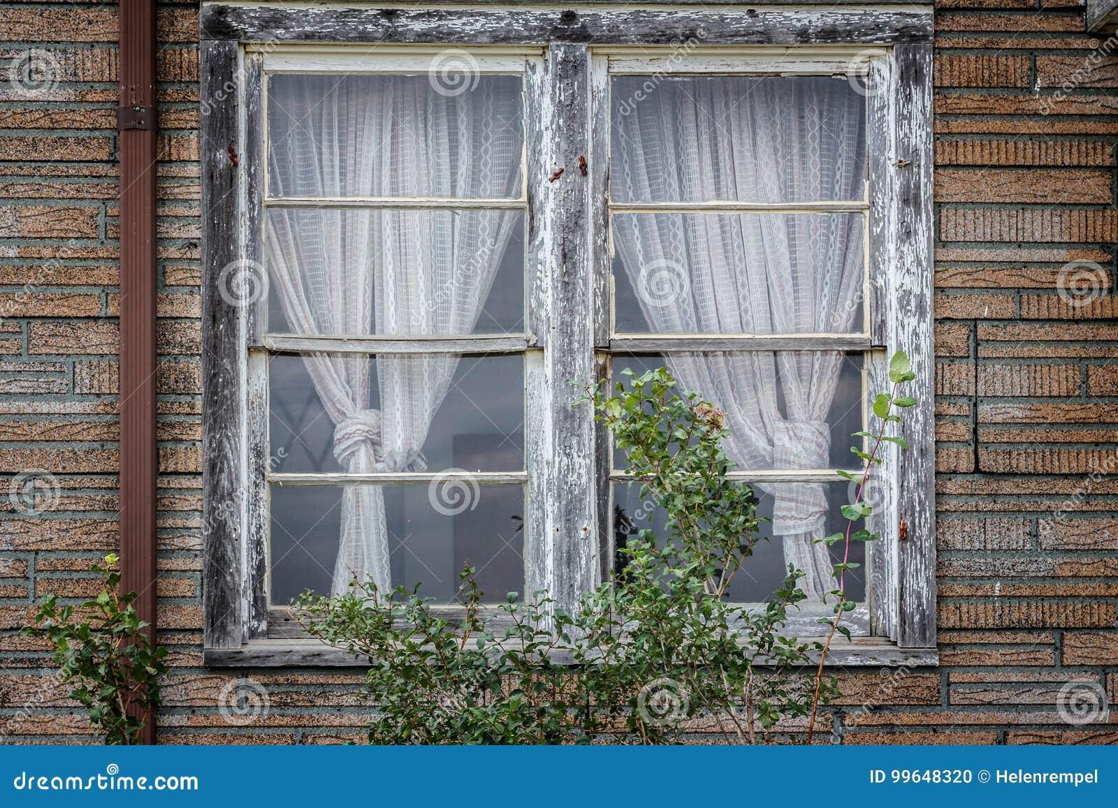 oude uitstekende dubbele vensters met oude gordijnen in een verlaten huis