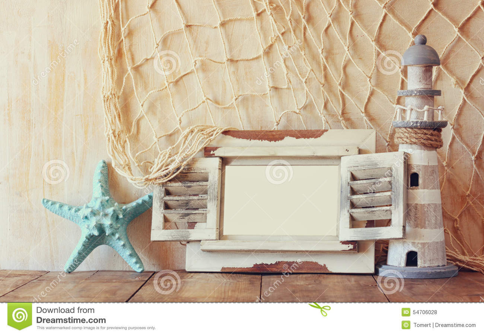 Oude uitstekende houten witte kader en vuurtoren op houten lijst wijnoogst gefiltreerd beeld zeevaartlevensstijlconcept