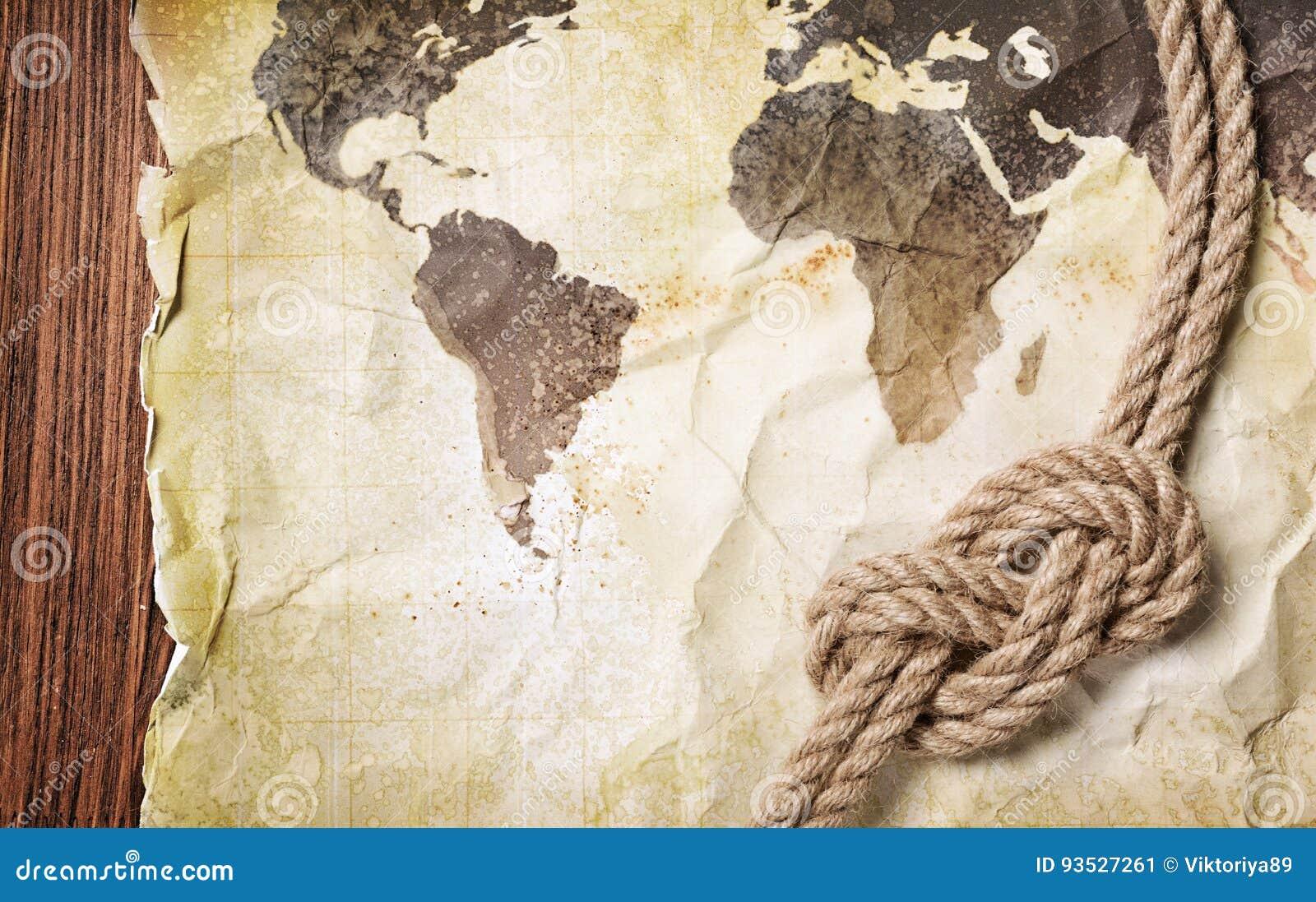 Oude uitstekende kaart van de wereld op geel retro bevlekt document met knoop van kabel
