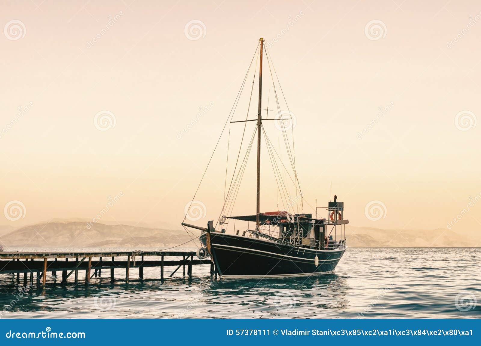 Oude varende boot bij zonsondergang