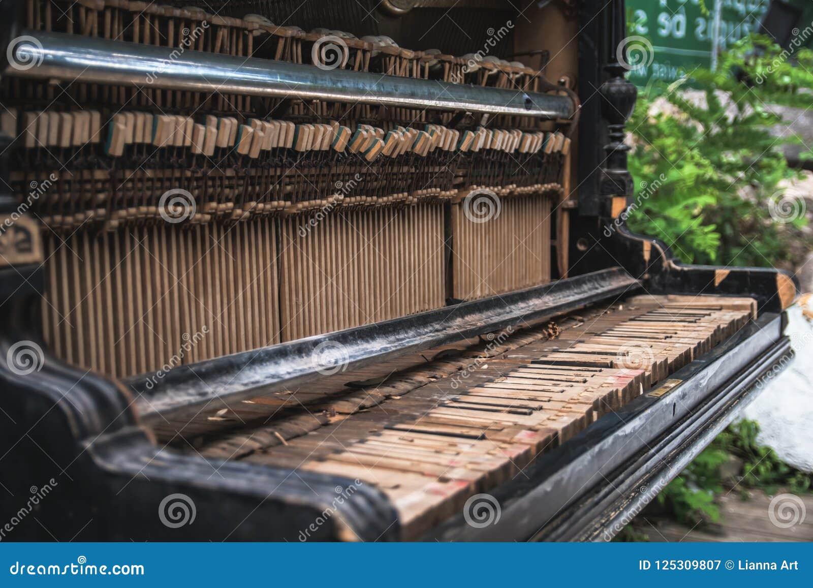 Oude verlaten gebroken piano op de straat
